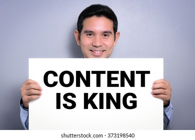 CONTENT IS KING, message on white cardboard shown by smiling man