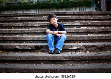 A content little Asian boy with an inquisitive look sitting on outdoor cement stairs, head tilted to the right.
