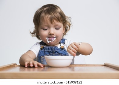 Content little guy enjoying his porridge or yogurt. He is wearing a white T-shirt and blue denim overalls.