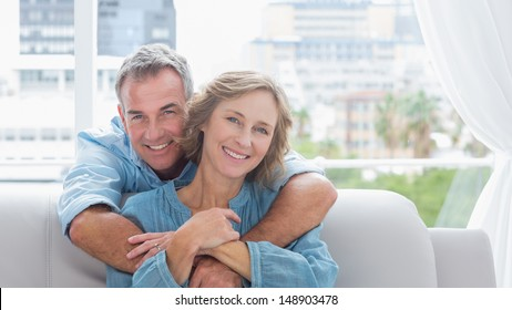 Content man hugging his wife on the couch smiling at camera at home in the living room