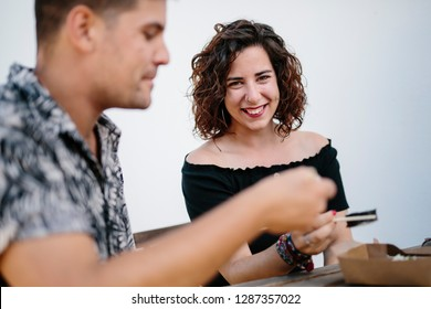 Content man and woman sitting outdoors eating sushi and spending time together happily