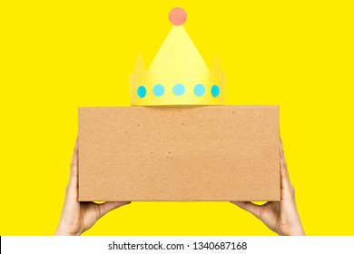 """Content marketing concept. Hand holding a box with the word """"CONTENT"""" in front and paper crown"""