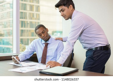 Content mentor praising new employee for good job. Sitting Afro American with tablet showing standing Indian paper graphs and tablet screen. Mentoring concept