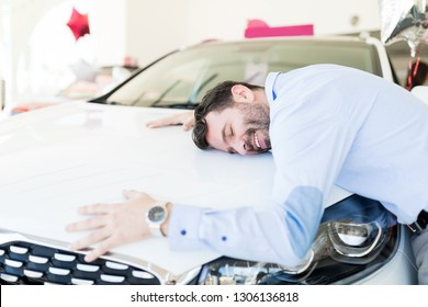 Content mid adult man hugging his new automobile at the dealership
