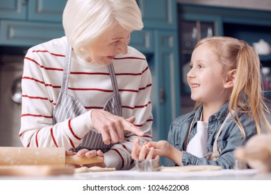 Content with result. Cheerful elderly woman pointing at a little cookie in the hands of her granddaughter and chuckling while they both making cookies together