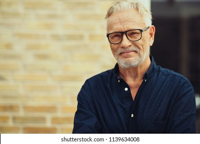 Content senior man with a beard and wearing glasses smiling while standing outside in front of his home