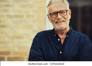 Content senior man with a beard and wearing glasses laughing while standing outside in front of his home