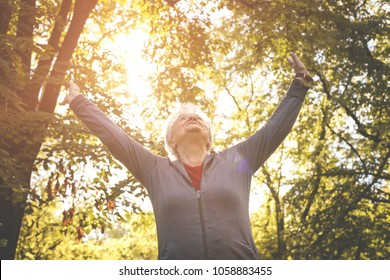 Content senior woman in sports clothing enjoying in forest after exercising