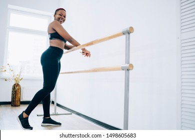 Content shapely flexible ethnic African American woman in black leggings and sneakers relaxing by barre in modern studio and looking at camera in daylight