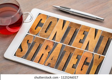 content strategy - word abstract in letterpress wood type printing blocks on a digital tablet with cup of tea