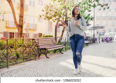 Content woman walking in city with smartphone and plastic cup. Pretty young lady going along walkway with trees and buildings in background. City walk concept. Full length front view.