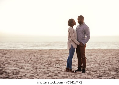 Content young African couple looking into each other's eyes while standing together on a sandy beach at dusk