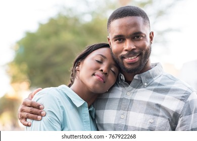 Content young African couple standing arm in arm while enjoying a sunny day together outside