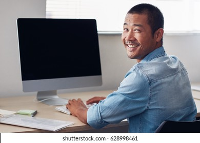 Content young Asian entrepreneur looking over his shoulder while working alone on a computer in a clean, modern office