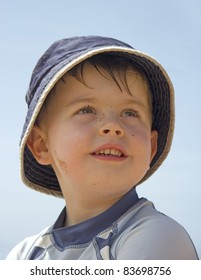 Content young boy sitting on beach wearing cool sun hat