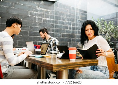 Content young brunette with smartphone posing at camera on background of colleagues in office.