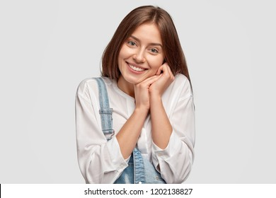 Content young female keeps hands near cheek, smiles positively, expresses happiness and truthful feelings, dressed in casual outfit, poses against white background, says: Mmm, its so pleasant!