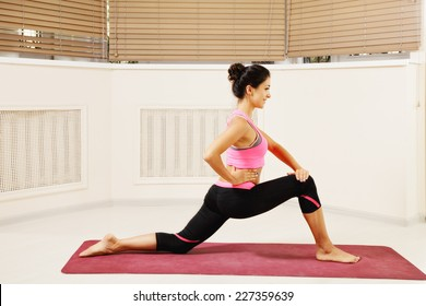 Contented brunette woman at stretching yoga pose