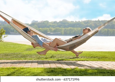 Contented couple relaxing in a hammock On grass and blue sky background