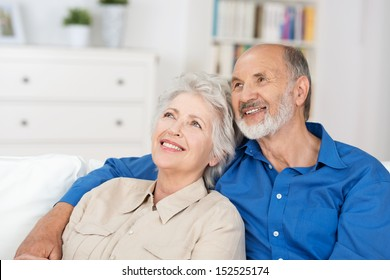 Contented elderly couple sitting in a close embrace in their living room reminiscing and recalling happy nostalgic memories