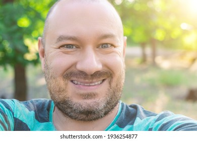 Contented plump unshaven middle-aged man smiling outdoors.