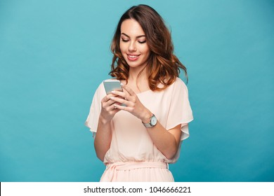 Contented smiling woman typing text message or scrolling through social networks using smartphone isolated over blue background