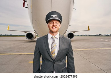 Contented stylish airline captain standing by a landed plane