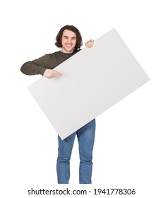Contented young man holding a big blank banner for advertising pointing and showing with index finger. Happy guy with an empty sheet for text announcements as a lottery winner with bank check prize