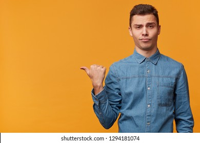 A contentedly pompous, arrogant guy isolated over yellow background casually draws your attention to what is on the left, shows with thumb finger on the empty space to copy.