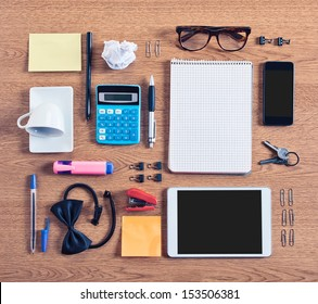 The contents of a business workspace organized and composed. Different business objects on wooden desk. Vintage effect.