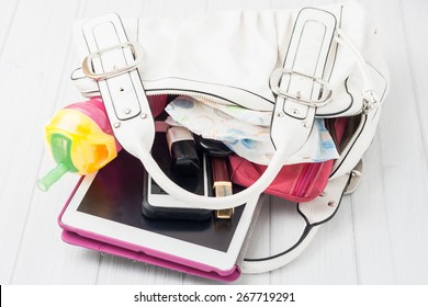 Contents of a woman's white shoulder bag on white background. Contents include: tablet, telephone, lipstick, nail polish, wallet, baby bottle and a diaper.
