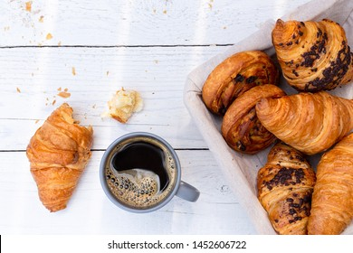Continental breakfast with black coffee and basket of pastries. Half eaten on white wood from above.