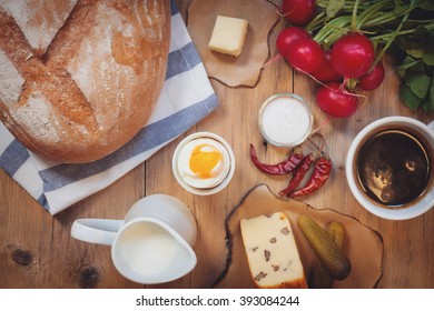Continental breakfast with black coffee and milk on old wooden table