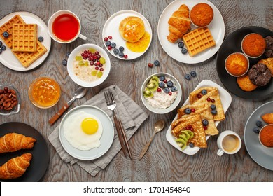 Continental breakfast captured from above (top view, flat lay). Coffee, tea, croissants, jam, egg, pancakes, maffins and oatmeal. Wooden background. Family breakfast table.
