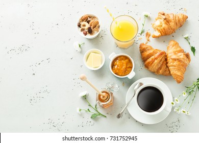 Continental breakfast captured from above (top view, flat lay). Coffee, orange juice, croissants, jam, honey and flowers. Grey stone worktop as background. Layout with free text (copy) space. - Shutterstock ID 731752945