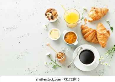 Kontinentales Frühstück von oben (Draufsicht, flache Lage). Kaffee, Orangensaft, Croissants, Marmelade, Honig und Blumen. Grauer Stein als Hintergrund.Layout mit freiem Text (Kopienraum).