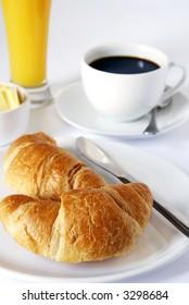 continental breakfast of coffee, orange juice and croissants