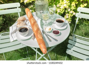 Continental breakfast on the garden table. Country lifestyle or weekend morning concept. Peaceful rural scenery.