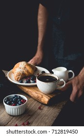 Continental breakfast on a tray: croissant, coffee, cream and berries. Man hands holding wooden tray with breakfast. Breakfast in bed