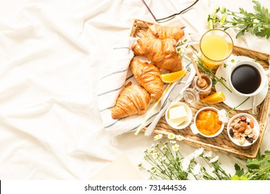 Continental breakfast on white bed sheets. Coffee, orange juice, croissants, jam, honey and flowers on wicker tray from above (top view, flat lay). Background layout with free text (copy) space.