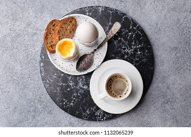 Continental breakfast with soft boiled eggs, slice of bread and freshly brewed coffee. Top view flat lay