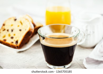 Continental breakfast table with cup of hot black coffee, milk, cakes and orange juice