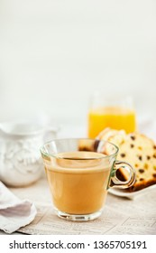 Continental breakfast table with cup of hot  coffee with milk, cakes and orange juice