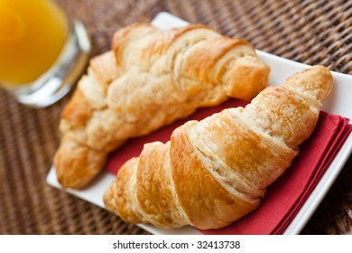 Continental breakfast with two croissants and a glass of orange juice