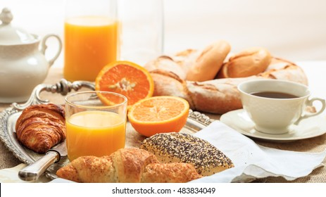 Continental healthy breakfast with fresh orange juice, croissants and coffee in an old silver tray