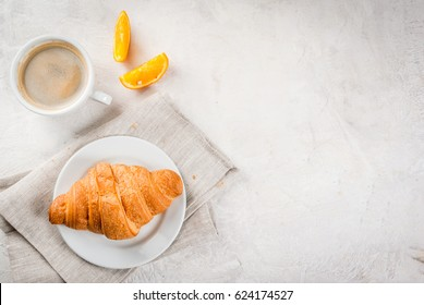 Continental traditional breakfast. Croissant, a cup of coffee and an orange. On a white stone concrete table. Copy space top view