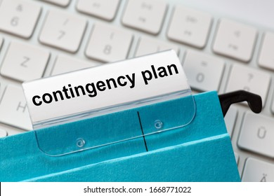 contingency plan is on a label of a blue hanging file. In the background a computer keyboard