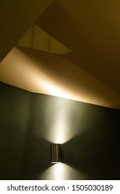 Contours and angles of stairwell walls and ceiling caught by single wall light