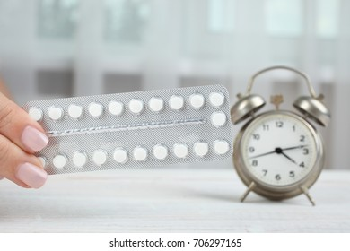 Contraceptive pills and alarm clock on the wooden table in front of the window.