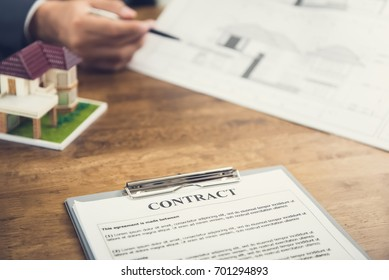 Contract agreement paper and  house model on the table with blur hand of businessman reviewing blueprint in background - real estate business concept
